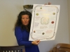 Hildur nám ukazuje plakát s knoflíky - kampaň zacílená na migrantky